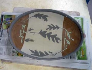 Greenware serving platter w/slip decoration.