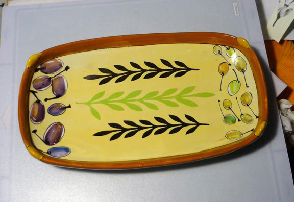 Majolica tray with painted image at the ends, unfired cut decal shapes in black and green in the center.